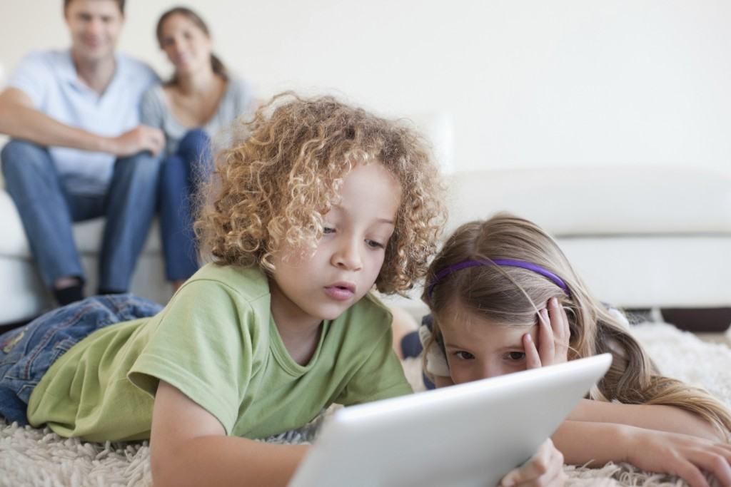 Young children using a tablet computer while their happy parents